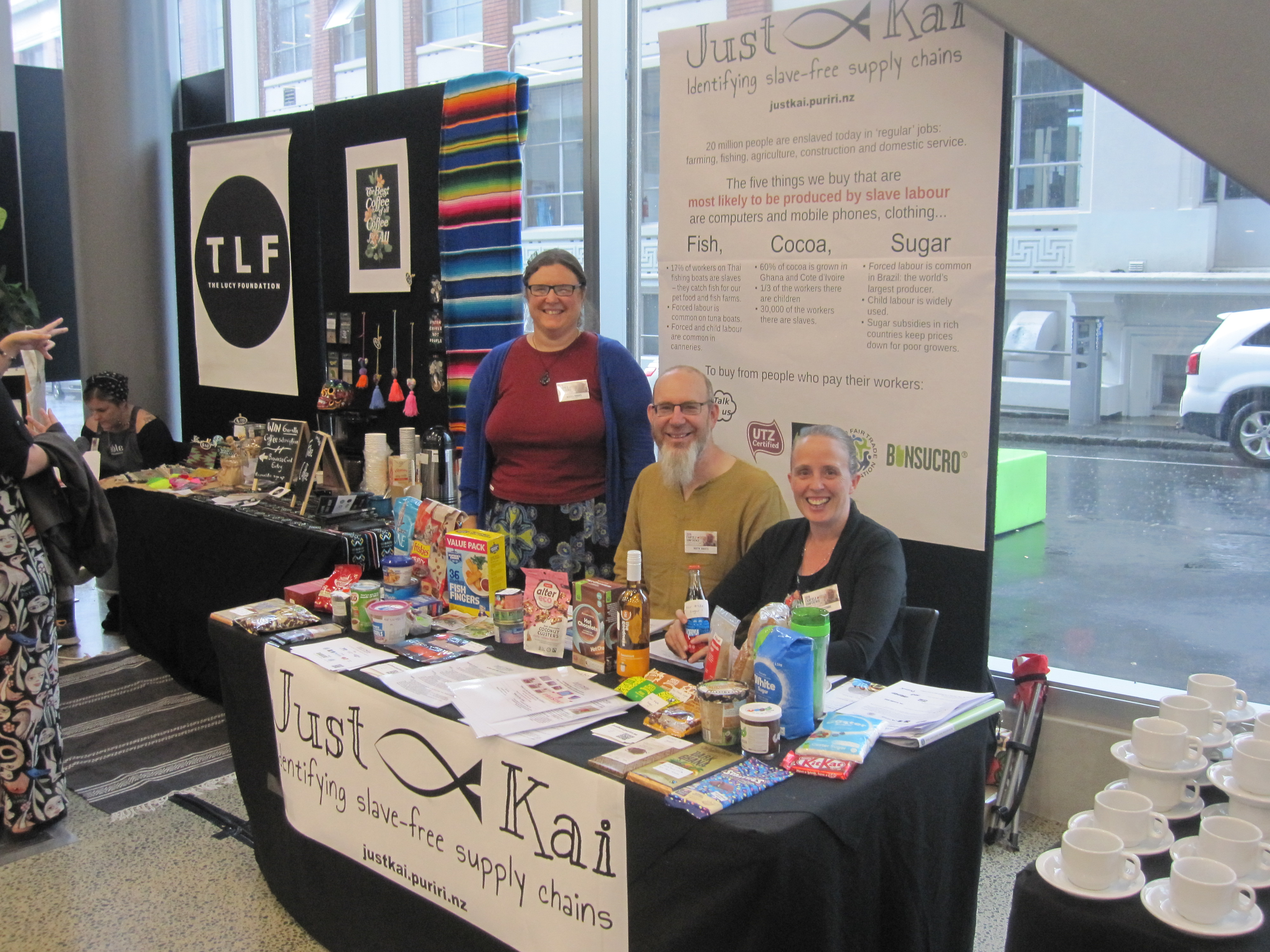 Heather, Martin and Anna behind the Just Kai table.  There are groceries on the table and a poster behind.