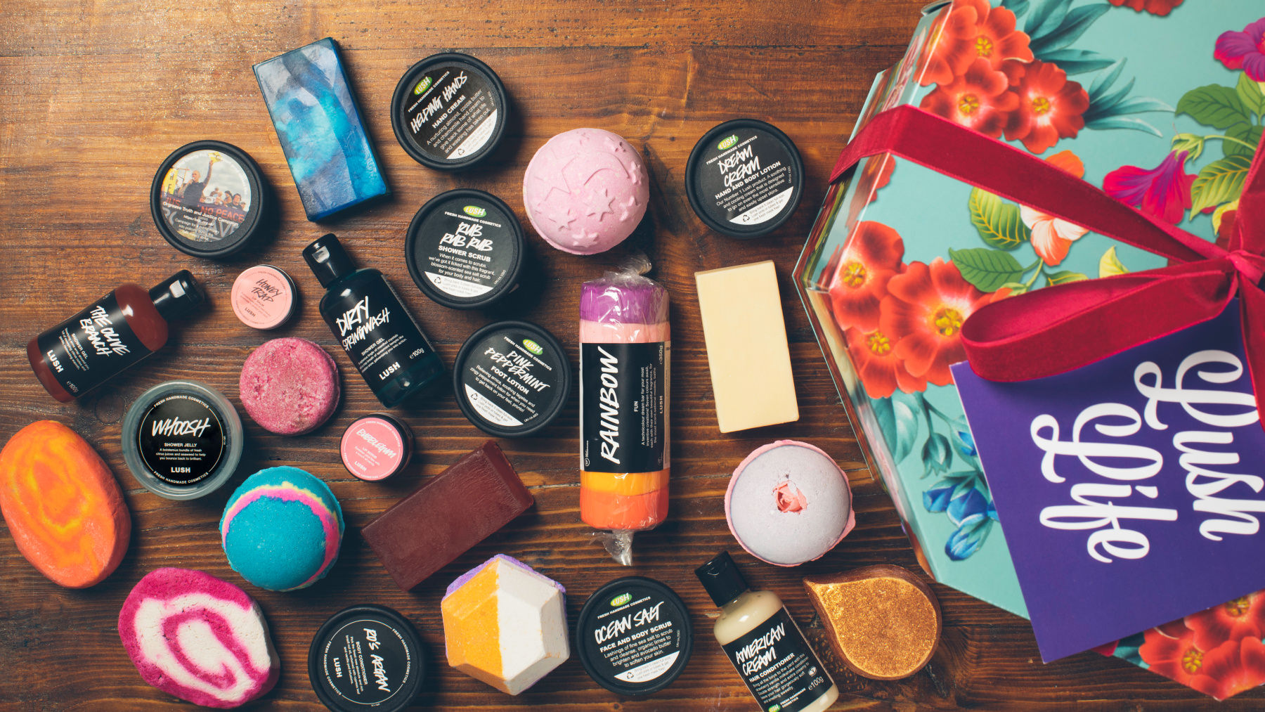 a selection of LUSH products scattered over a wooden table