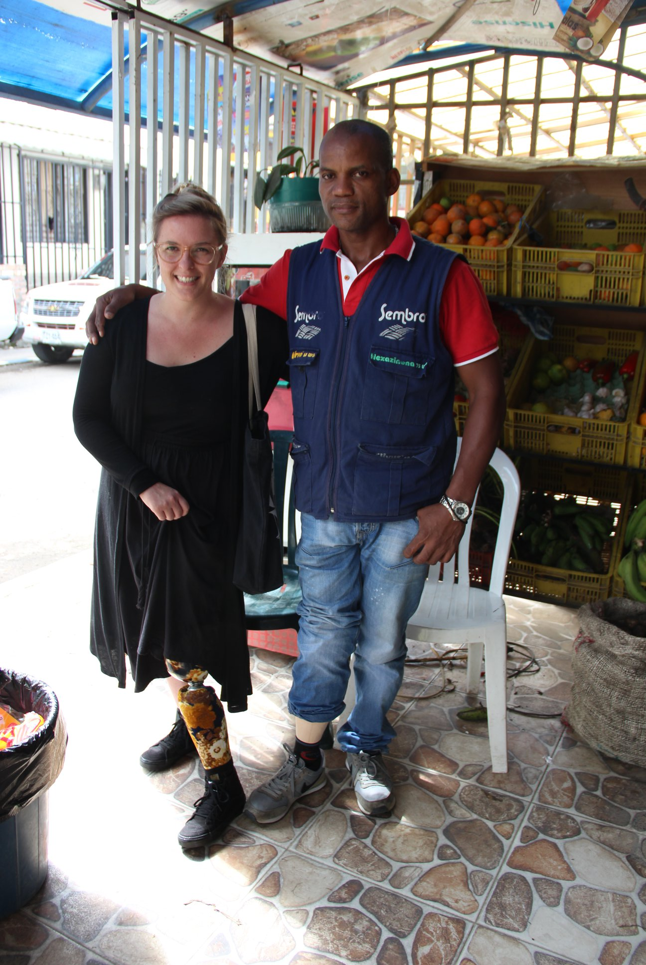 Robbie with a Latin American man, both showing off their prosthetic legs